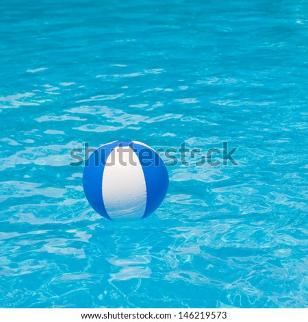 White and blue beach ball floating on a sparkling blue swimming pool  - stock photo