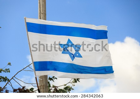 White and blue flag of Israel waving in the wind - stock photo