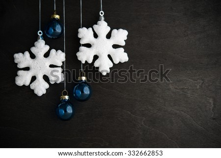 White and blue xmas ornaments on black wooden background. Merry christmas card. Winter holidays. Xmas theme. Happy New Year. - stock photo