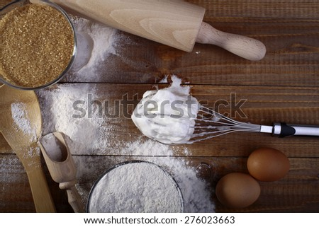 White and brown products and appliances such as flour cane sugar frothed eggs rolling pin beater and wooden spoon on table top, horizontal picture - stock photo