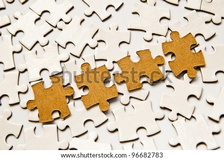 white and brown puzzle pieces as a background - stock photo
