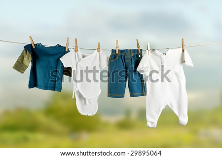 White and colored baby laundry hanging on a clothesline - stock photo