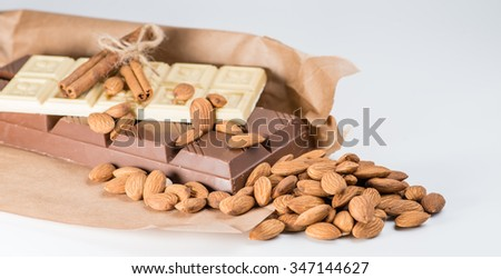 white and dark chocolate, almonds, cinnamon, cocoa. shallow DOF - stock photo