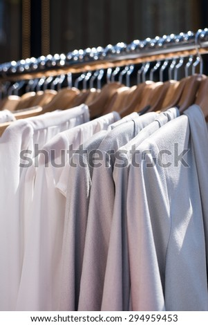 white and gray tone clothes hanging on a rack in a designer clothes store, selective focus, vertical - stock photo
