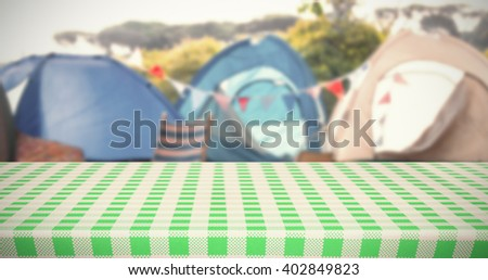 white and green tablecloth against empty campsite at music festival - stock photo