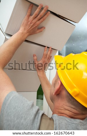 White and heavy boxes falling on worker with yellow helmet - stock photo