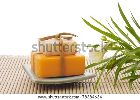 white and orange soaps with flower on white - stock photo