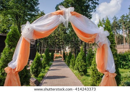white and orange textile wedding arch in the park - stock photo