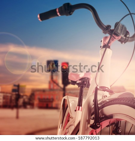 white and pink bike with sunset in city  - stock photo