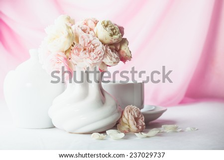White and pink roses in a vase on the table - stock photo