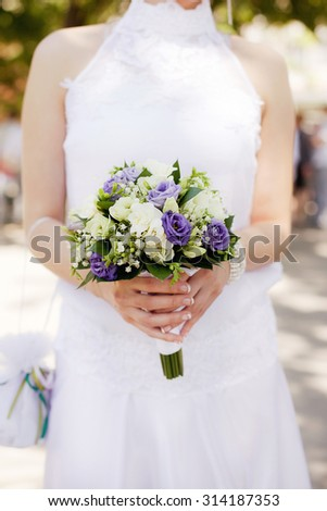 White and purple bouquet in bride's hands with roses, eustoma and lily of the valley. Vertical closeup image - stock photo