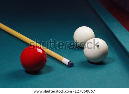 White and red carom balls with billiard cue on pocketless table - stock photo