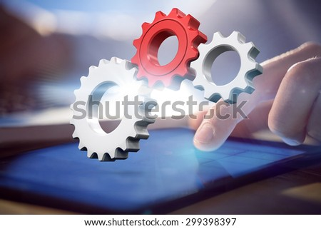 White and red cogs and wheels against businessman using laptop and tablet at desk - stock photo