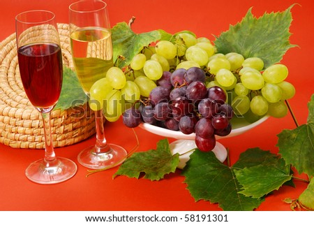 white and red grape cluster and glasses of wine on brown background - stock photo