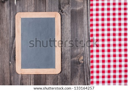 White and red tablecloth, black board on wooden table background - stock photo