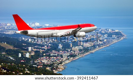 White and red wide-body passenger plane. Aircraft is flying over the seaside city. - stock photo