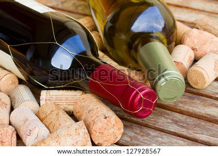 white and red wine bottles with corks on wooden table - stock photo