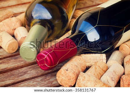white and red wine bottles with corks on wooden table, retro toned - stock photo