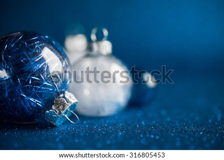 White and silver christmas ornaments on dark blue glitter background with space for text. Merry christmas card. Winter holidays. Xmas. - stock photo