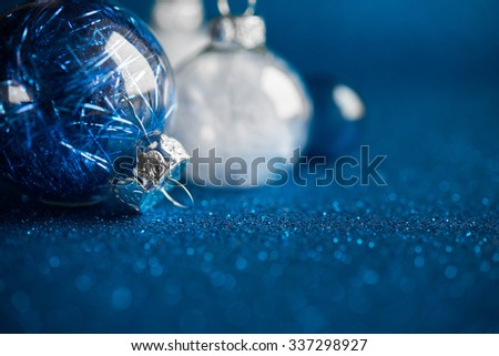 White and silver christmas ornaments on dark blue glitter background with space for text. Merry christmas card. Winter holidays. Xmas theme. Happy New Year. - stock photo