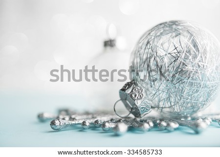 White and silver xmas ornaments on glitter bokeh background. Merry christmas card. Winter holidays. Xmas theme. Happy New Year. - stock photo
