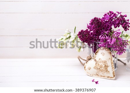 White and violet lilac flowers and decorative  heart  on white painted wooden planks. Selective focus. Place for text. - stock photo