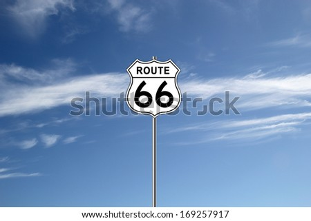 White and white Route 66 Road Sign isolated on blue sky background. - stock photo