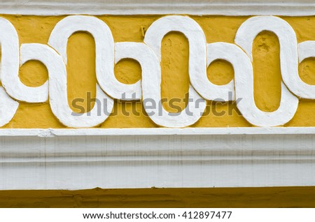 white and yellow concrete ornament on the wall, India - stock photo