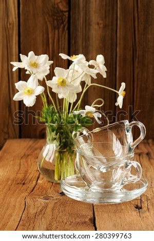 White anemones and two glass cups and saucers on wooden background copyspace - stock photo