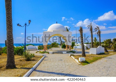 White arabic arch with palms in Hammamet Tunisia. - stock photo