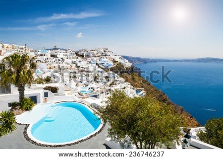 White architecture on Santorini island, Greece. Swimming pool in luxury hotel. Beautiful view on the sea - stock photo