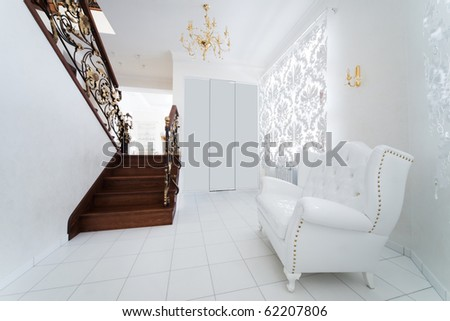 white armchair in the hallway with a staircase - stock photo