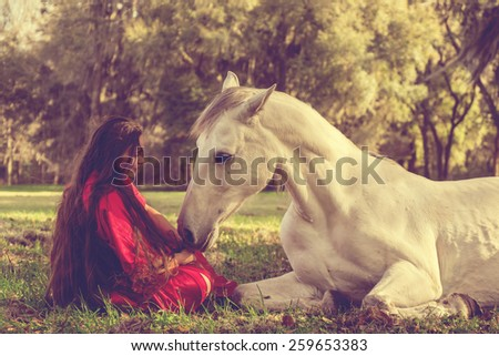 White Azteca horse mare stallion equine lying down in field pasture meadow and young woman girl in red dress gown looking romantic serene innocent trusting beautiful connected and vintage retro filter - stock photo