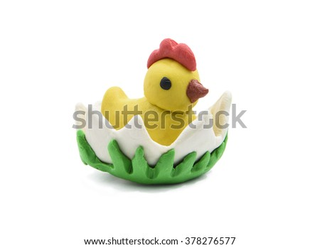 White baby chicken with Easter eggs colour plasticine crafts on a white background. - stock photo