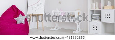 White baby room with cradle, shelving unit and pink sack chair - stock photo