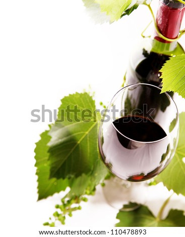 White background with goblet, bottle and vine - stock photo