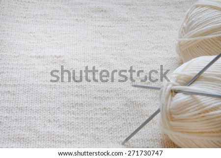 White balls of yarn and knitting on a wool background - stock photo