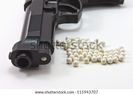 White balls with an black gun (airsoft) isolated on white - stock photo