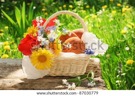 White basket with pasties and flowers on old table in a garden at a summer day - stock photo