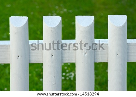 White batten fence with green grass on background - stock photo