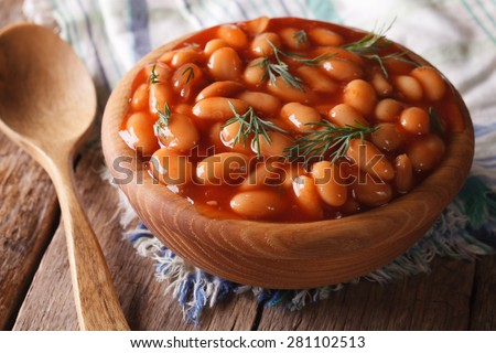 white beans in tomato sauce in a wooden bowl closeup. horizontal