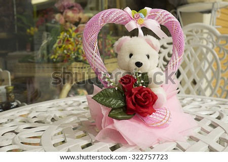 White bear doll and pink heart with red rose on the vintage white table. Love concept, wedding concept, souvenir concept, congratulation - stock photo