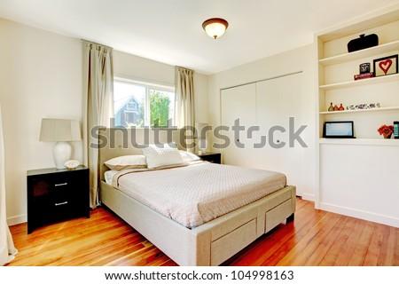 White bedroom with hardwood cherry floor and black nightstand. - stock photo