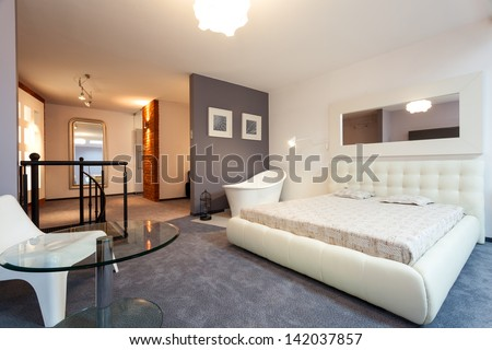 White bedroom with mirror in the loft - stock photo
