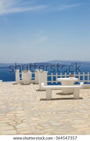 white bench against sea and volcano caldera, beautiful details of Santorini island, Greece - stock photo