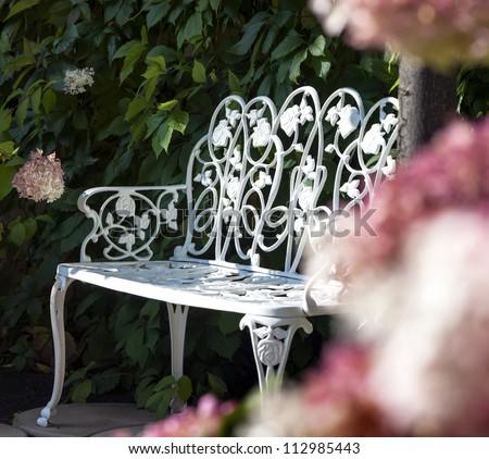 White bench in a summer garden - stock photo
