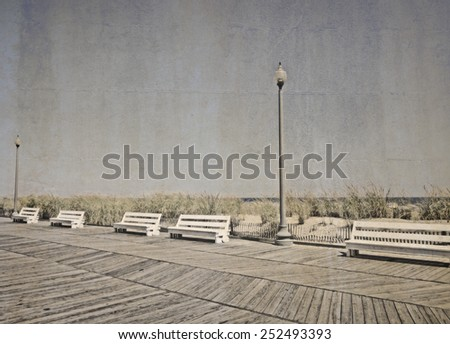 White benches on the boardwalk with an aged vintage effect applied. - stock photo