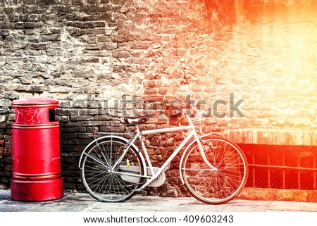 White bicycle standing on the street. Filtered image. - stock photo
