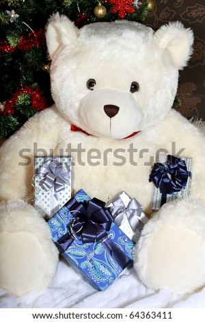 White big teddy bear holding a presents and sitting at the Christmas Tree - stock photo