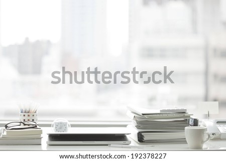 White binders, laptop and cup on a white desk. - stock photo